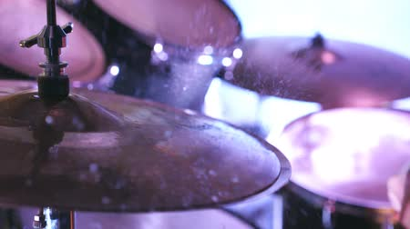Male hand of professional drummer hits with drumstick on cymbal and water drops splashing from plate. Unrecognizable man playing on wet drum during rock concert indoor. Side view Close up Slow motion