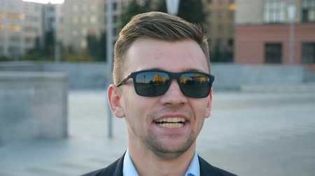 Portrait of tired businessman in sunglasses yawning outdoor. Exhausted sleepy man opening his mouth outside. Angry guy yelling to camera. Handsome male entrepreneur screaming at city street. Close up