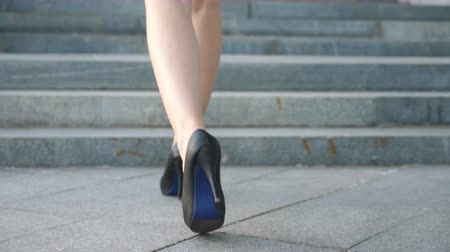 エリート : Female legs in high heels shoes walking on the stairs. Feet of businesswoman stepping up on stairway. Elegant woman climbing at staircase. Young girl stepping at city street. Close up Slow motion 動画素材