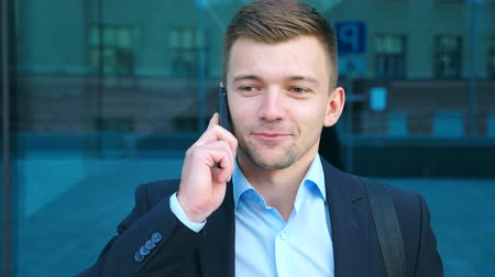 воротник : Portrait of handsome businessman talking on phone near office. Young business man speaking on cellphone and having positive emotions. Guy is happy with conversation. Slow motion Close up