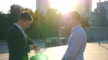 divergeren : Two business men standing outdoor and talking. Businessmen shaking hands of each other outdoor then farewell and diverge. Communication of colleagues. Shaking of male arms outside. Slow motion Closeup
