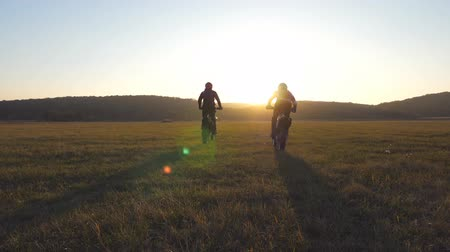 enduro : Two motorcyclists passing through large field with beautiful landscape at background. Bikers rides into sunset. Two friends riders having active rest on nature. Extreme sport concept. Slow motion