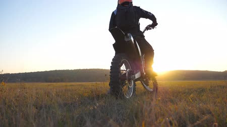 enduro : Biker stopped at the field to wait for his friend. Sportsman at the meadow. Man enjoying ride on his motorcycle. Beautiful sunset at background. Slow motion Close up Back view Stock Footage