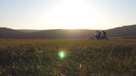 enduro : Two motorcyclists passing through large field with beautiful sunset at background. Warm summer sun lights up green vegetation of field. Friends having active rests on nature. Slow motion Stock Footage