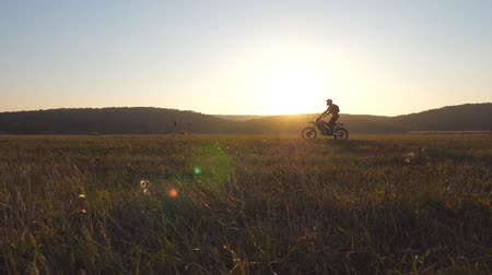 enduro : Motorcyclist passing through large field with beautiful sunset at background. Warm summer sun lights up green vegetation of field. Concept of active rest on nature. Slow motion Dolly shot