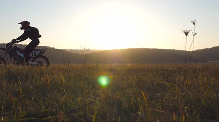enduro : Two motorcyclists passing through large field with beautiful sunset at background. Warm summer sun lights up green vegetation of field. Friends active rests on nature. Extreme sport. Slow motion