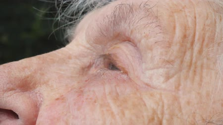 verdadeiro : Close up face of sad old woman with deep wrinkles is crying. Portrait of unhappy grandmother. True sincere weeping of elderly lady. Side view Slow motion Stock Footage