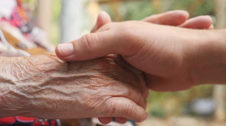 rebuliço : Close up of young male and wrinkled hands stroking each other outdoor. Family spending time together outside. Concept of care and love. Side view Slow motion Stock Footage