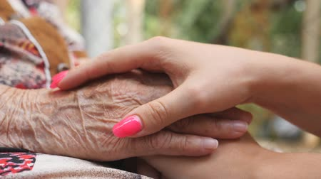 cuidados com a pele : Old wrinkled and young female hands comforting and stroking each other outdoor. Granddaughter and grandmother spending time together. Caring and loving concept. Close up Side view Slow motion