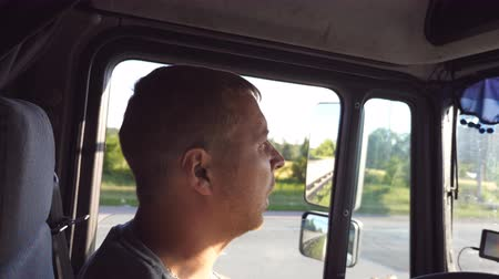 semi profile : Man talking and driving truck through countryside on a warm summer day. Profile of truck driver. Trucker riding at the car. Side view Close up Slow motion
