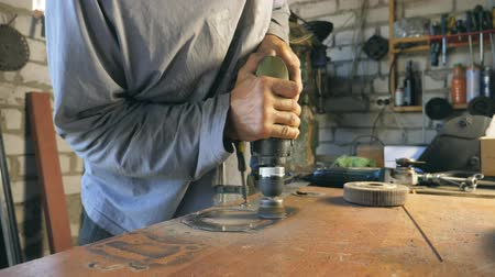 repairer : Hands of mechanic hold tool during operation. Man works in his garage or workshop. Worker processes detail on desktop. Hard work concept. Slow motion Close up