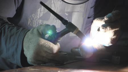 kaynakçı : Close up of welder doing welding work using professional equipment and protective mask in garage or workshop. Man welds metal parts. Flashes from welding work indoor. Slow motion