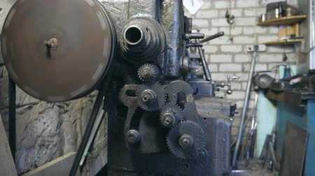 pinion : Metal workbench working in garage or workshop. Gears rotate touching each other. Front view Slow motion Close up