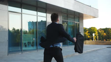 aktatáska : Unrecognizable businessman with briefcase runs down city street. Business man late for meeting. Successful man in suit jogging near modern building. Guy in hurry to appointment. Back view Slow motion