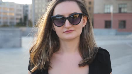 pracodawca : Portrait of young businesswoman in sunglasses walking in city street. Attractive business woman looking at camera. Face of confident girl commuting to work. Blurred background.Close up Slow motion
