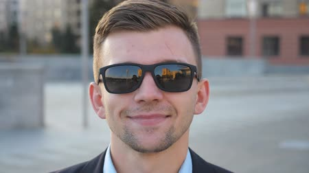 работодатель : Portrait of happy businessman in sunglasses with cityscape at background. Handsome business man looking at the camera and smiling. Face of cheerful guy. Blurred background. Slow motion Close up