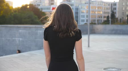 брюнет : Young unrecognizable girl in black dress walking along urban street. Attractive businesswoman going in city. Girl stepping outdoor. Rear back view Slow motion Close up