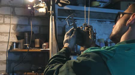 repairer : Male mechanic in glasses carefully examines vehicle detail. Repairer works in garage or workshop. Worker uses tool for his job. Side view Slow motion Close up