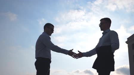 köszönt : Two successful businessmen meeting in city and greet each other. Young male colleagues shaking hands outdoor. Handshake of business partners outdoor. Blue sky at background. Slow motion Low angle view