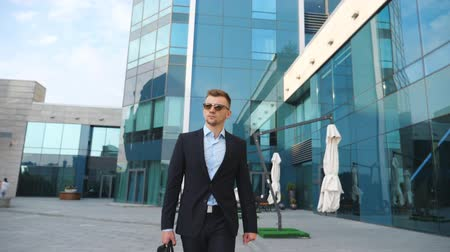 aktatáska : Young businessman in a black suit with briefcase walking along modern office building. Confident male entrepreneur with bag goes to job. Handsome guy commuting to work. Slow motion Close up