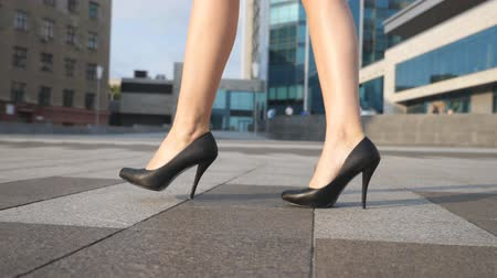 high heel shoe : Feet of young businesswoman in footwear on high-heeled going in urban street. Slim female legs in black shoes on high heels walking at city square. Elegant girl stepping to work. Slow motion Close up