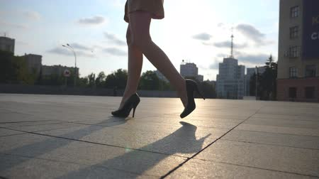 high heel shoe : Slim female legs in black shoes on high heels walking on city square at sunset. Feet of young businesswoman in footwear on high-heeled going in urban street. Low angle view Slow motion Close up Stock Footage