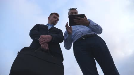 use computer : Young businessman showing a presentation on screen of tablet pc to his colleague in city. Successful entrepreneurs working on digital tablet with blue sky at background. Low angle view Slow motion