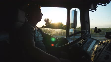 semi profile : Man driving a truck and carefully watching the road. Caucasian guy is riding through the countryside on the sunset background. Profile of lorry driver inside the cab. Side view Slow motion Close up Stock Footage