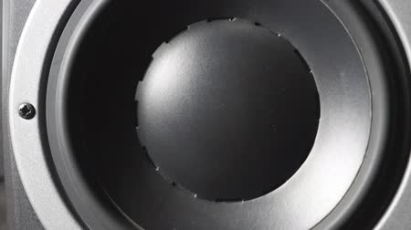 hi fi : Close up of moving professional sub-woofer on recording studio. A black round audio speaker pulsating and vibrating from sound on low frequency. Work of high fidelity loudspeaker membrane. Slow motion