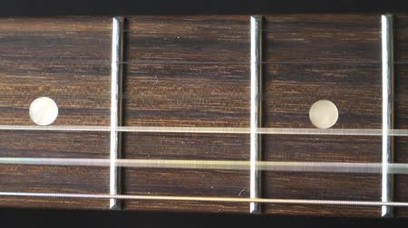 strum : Close up of trembling guitar strings against fret. Chords being strummed and vibrating during playing. Beautiful background with wooden texture. Music performance. Slow motion Stock Footage