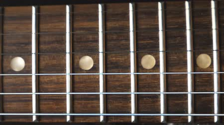 strum : Close up of chords being strummed and vibrating during playing. Trembling guitar strings against fret. Beautiful background with wooden texture. Music performance. Slow motion Stock Footage