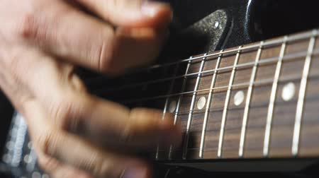 akusztikus : Close up fingers of guitarist strumming the strings. Hand of male musician playing on electric guitar. Arm of adult man plays on a musical instrument. Guy composing a new melody. Slow motion