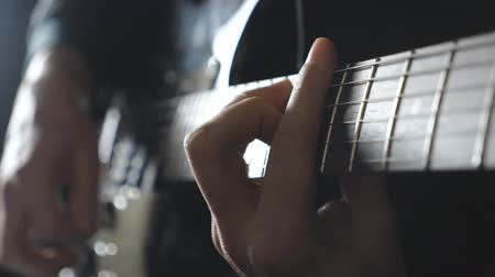 rocker : Arms of male musician playing on electric guitar. Close up fingers of guitarist strumming the strings. Hands of guy performing solo of rock music. Adult man plays on a musical instrument. Slow motion