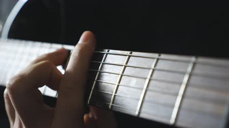 rockero : Close up male fingers of guitarist strumming the strings. Hand of guy performing solo of rock music. Arm of musician playing on electric guitar. Adult man composing a new melody. Slow motion
