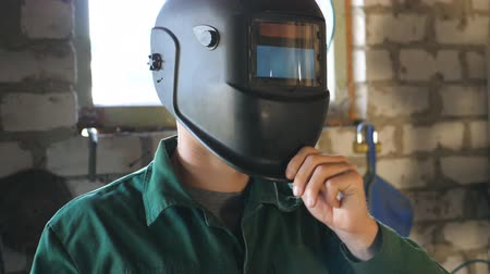 repairer : Welder opens mask and looking at camera. Portrait of handsome man with beard working in his garage or workshop. Slow motion Close up