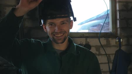 kaynakçı : Smiling welder looks into camera and lowers mask to get to work. Happy man with beard working in his garage or workshop. Guy laughs and enjoys life. Slow motion Close up Stok Video