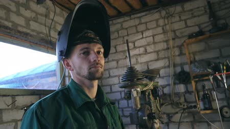 repairer : Tired mechanic looking at camera. Man in workwear working in his garage or workshop. Slow motion Close up Side view Stock Footage