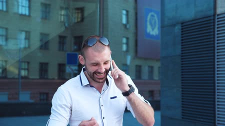 ouvido : Handsome businessman talking on phone near office and having positive emotions. Young business man heard good news on cellphone and rejoices outdoor. Guy is happy with conversation. Slow mo Close up Vídeos