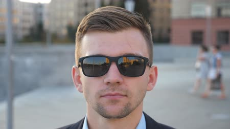 pracodawca : Portrait of young businessman in sunglasses walking along city street. Handsome business man looks at camera strolling at town square. Face of confident guy commuting to work. Slow motion Close up Wideo