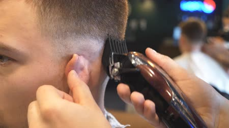 navalha : Close up arms of barber making male haircut to customer with clipper in salon. Hands of hairstylist cutting hair of young client with electric razor in barbershop. Barber shaving man with trimmer