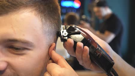 shaver : Close up hands of hairstylist cutting hair of young client with electric razor in barbershop. Arms of barber making male haircut to customer with clipper in salon. Barber shaving man with trimmer