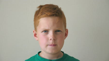 szeplők : Portrait of serious red hair boy with freckles. Adorable handsome baby looking into camera indoor. Close up emotions of male child with sad expression on face. Slow motion Stock mozgókép