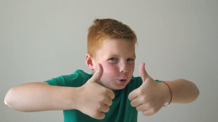 rejoice : Adorable baby rejoicing achievement and showing thumbs up. Close up emotions of male child with joy expression on face. Portrait of handsome happy red hair boy with freckles indoor. Slow motion