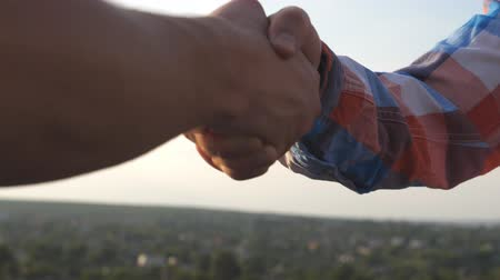 symbol of respect : Friendly handshake of two unrecognizable men on cityscape background. Close up of men greeting with handshake. Two good friends having firm handshake outdoor. Friendship concept. Side view Slow motion
