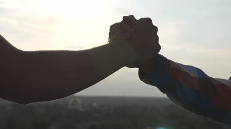 symbol of respect : Friendly handshake of two unrecognizable men on cityscape background. Close up of men greeting with handshake. Two good friends having firm handshake outdoor. Friendship concept. Slow motion