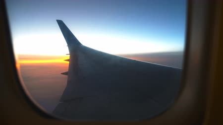 чирок : View from airplane window to sunrise or sunset. Wing of plane flying above the clouds with sun light. Aircraft flight at sky. Concept of traveling by air. Trip by airliner with beautiful background