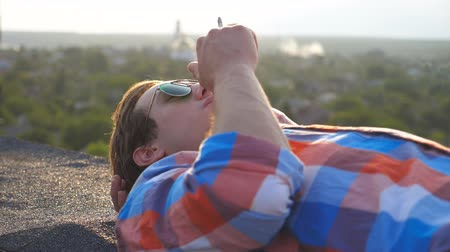 alışkanlık : Handsome man in sunglasses lying on roof and smoking cigarette at cityscape background. Young guy relaxing and enjoying moment outdoor. Beautiful view. Slow motion Close up