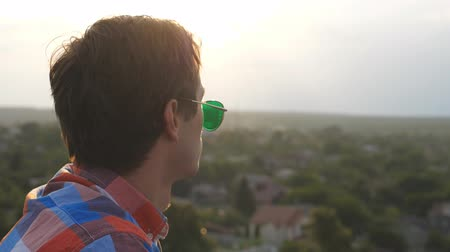 hayran olmak : Profile of handsome man in sunglasses standing on roof and admiring beautiful view at evening time.Young guy resting and enjoying moment outdoor. Dolly shot Slow motion Close up Stok Video