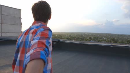 вести : Guy holds hand of his boyfriend and runs to edge of roof to admire the view. Follow me shot of young man pull his lover on rooftop. Beautiful landscape at background. Point of view Slow motion Стоковые видеозаписи