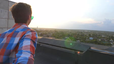telhado : Guy holds hand of his boyfriend and runs to edge of roof to admire the view. Follow me shot of young man pull his lover on rooftop. Beautiful landscape at background. Point of view Slow motion Stock Footage